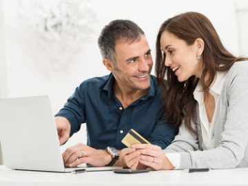 Portrait Of Happy Couple Shopping Online Using Laptop And Credit Card